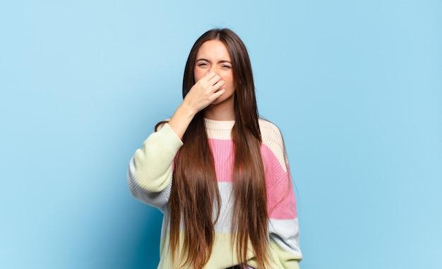 Młoda, całkiem zwyczajna kobieta czuje się zdegustowana, trzyma nos, aby uniknąć nieprzyjemnego zapachu smrodu