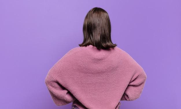Młoda, całkiem zwyczajna kobieta czuje się zdezorientowana lub pełna lub ma wątpliwości i pytania, zastanawia się, z rękami na biodrach, widok z tyłu