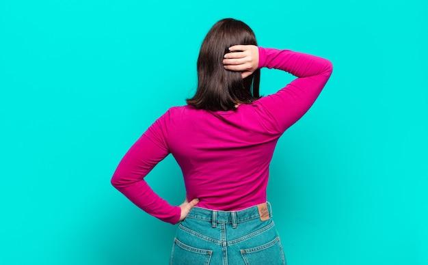 Młoda, całkiem zwyczajna kobieta myśli lub wątpi, drapie się po głowie, czuje się zdezorientowana i zdezorientowana