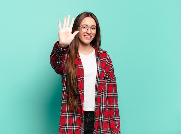 Młoda, całkiem zwyczajna kobieta uśmiechająca się i wyglądająca przyjaźnie, pokazująca numer pięć lub piąty z ręką do przodu, odliczając w dół