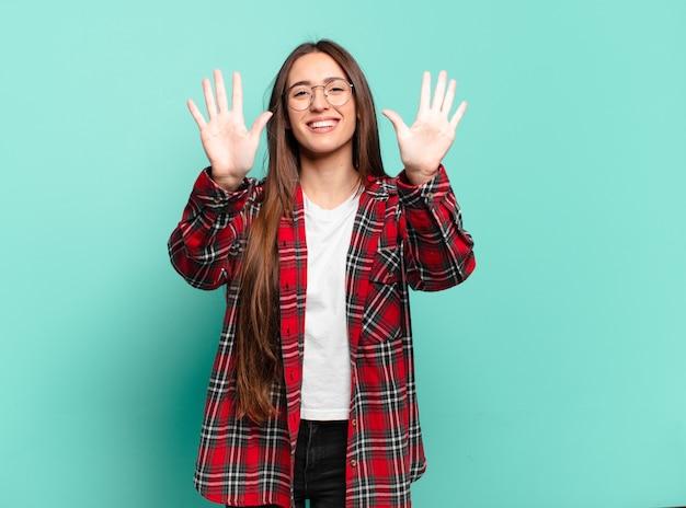 Młoda, całkiem zwyczajna kobieta, uśmiechnięta i wyglądająca przyjaźnie, pokazująca liczbę dziesięć lub dziesiątą ręką do przodu, odliczając w dół