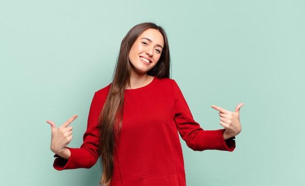 Młoda, całkiem zwyczajna kobieta wyglądająca na dumną, arogancką, szczęśliwą, zaskoczoną i zadowoloną, wskazującą na siebie, czującą się jak zwycięzca