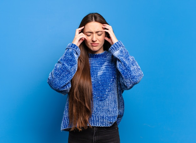 Młoda, całkiem zwyczajna kobieta wyglądająca na zestresowaną i sfrustrowaną, pracująca pod presją, z bólem głowy i z problemami