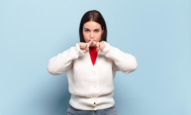 Młoda, całkiem zwyczajna kobieta, wyglądająca poważnie i niezadowolona, z obiema palcami skrzyżowanymi z przodu w odrzuceniu, prosząca o ciszę