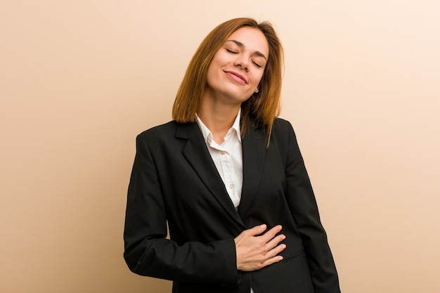 Młoda caucasian biznesowa kobieta dotyka brzuch, uśmiecha się delikatnie, jedzący i satysfakci pojęcie.