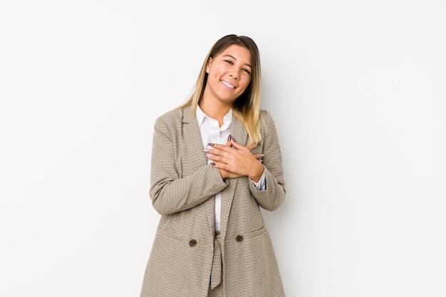 Młoda caucasian biznesowa kobieta odizolowywająca ma życzliwy wyraz, naciska dłoń do klatki piersiowej. koncepcja miłości.