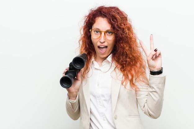 Młoda caucasian biznesowa rudzielec kobieta trzyma lornetkę pokazuje zwycięstwo znaka i ono uśmiecha się szeroko.