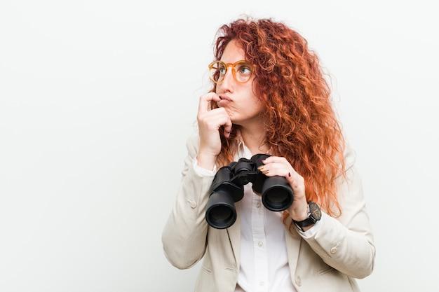 Młoda caucasian biznesowa rudzielec kobieta trzyma lornetki relaksował główkowanie o coś patrzeje odbitkową przestrzeń.