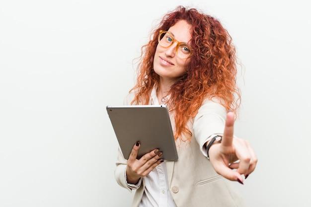 Młoda caucasian biznesowa rudzielec kobieta trzyma pastylkę rozochoconych uśmiechy wskazuje przód.