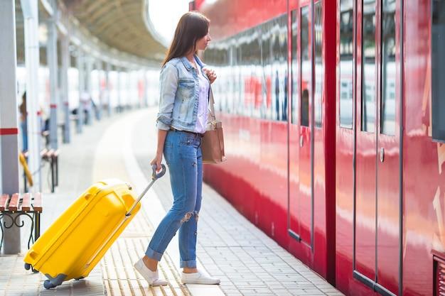 Młoda caucasian dziewczyna z bagażem przy stacją podróżuje pociągiem