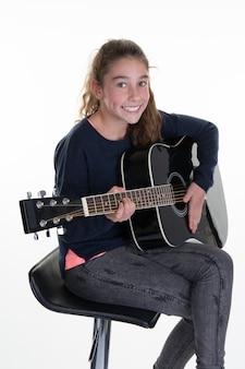 Młoda caucasian dziewczyna z gitarą akustyczną, odizolowywającą na białym tle