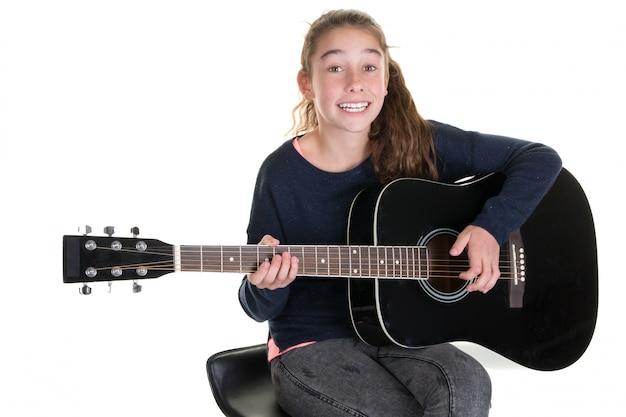Młoda caucasian dziewczyna z gitarą akustyczną, odizolowywającą na bielu