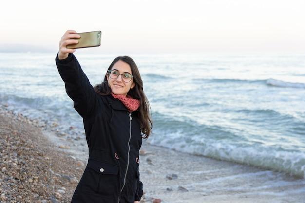 Młoda caucasian dziewczyna z szkłami robi selfie na plaży w zimie