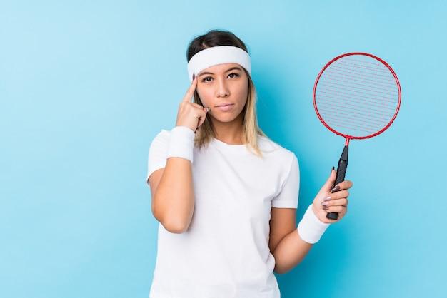 Młoda caucasian kobieta bawić się badminton odizolowywającą wskazuje świątynię z palcem, główkowanie, skupiający się na zadaniu.