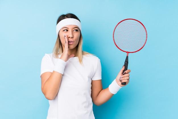 Młoda caucasian kobieta bawić się badminton odizolowywającego mówi sekretną gorącą hamującą wiadomość i patrzeje na boku