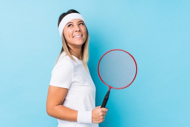 Młoda caucasian kobieta bawić się badminton odizolowywającego patrzeje na boku uśmiechniętych, rozochoconych i przyjemnych.