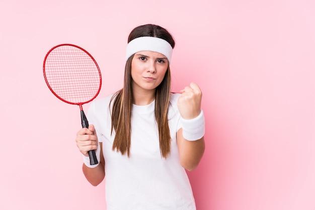 Młoda caucasian kobieta bawić się badminton odizolowywającego pokazywać pięść, agresywny wyraz twarzy.