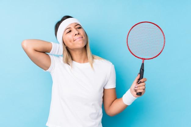 Młoda caucasian kobieta bawić się badminton odizolowywał macanie plecy głowę, główkowanie i robić wyborowi.