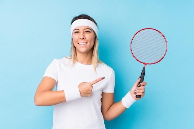 Młoda caucasian kobieta bawić się badminton odizolowywał ono uśmiecha się i wskazuje na boku, pokazuje coś przy pustą przestrzenią.