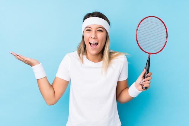 Młoda caucasian kobieta bawić się badminton odizolowywał otrzymywający przyjemną niespodziankę, podekscytowany i podnoszący rękę.