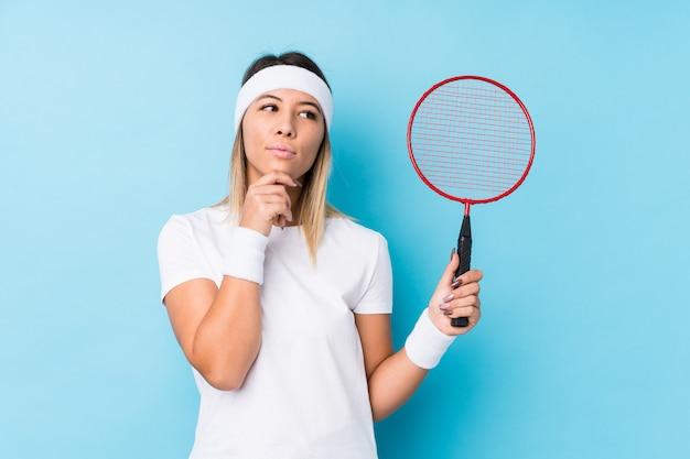 Młoda caucasian kobieta bawić się badminton odizolowywał patrzeć z ukosa z wątpliwym i sceptycznym wyrażeniem.
