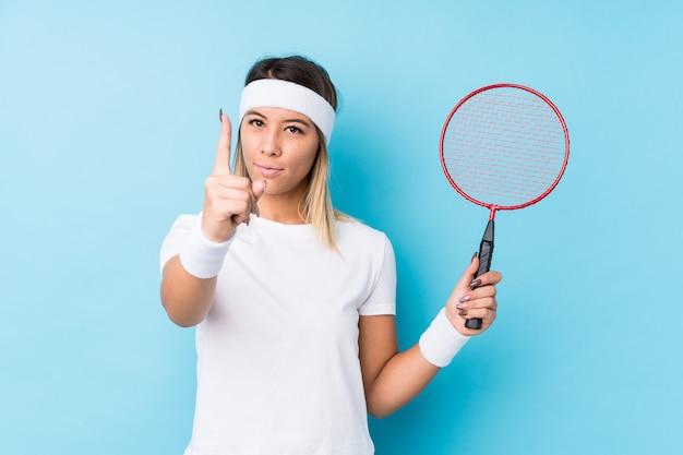 Młoda caucasian kobieta bawić się badminton odizolowywał pokazywać liczbę jeden z palcem.