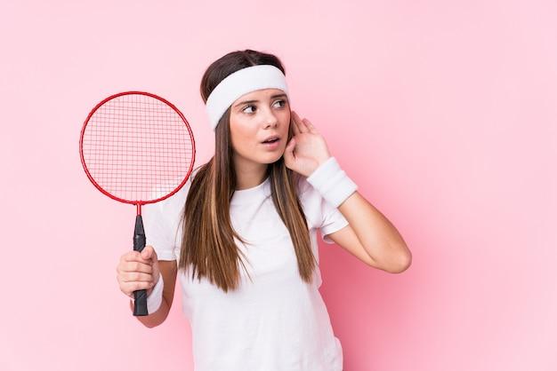 Młoda caucasian kobieta bawić się badminton odizolowywał próbować słuchać plotki.