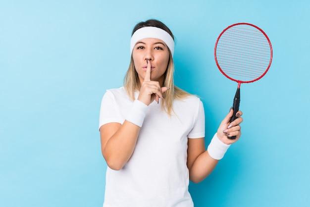 Młoda caucasian kobieta bawić się badminton odizolowywał utrzymywać sekret lub pytać o ciszę.