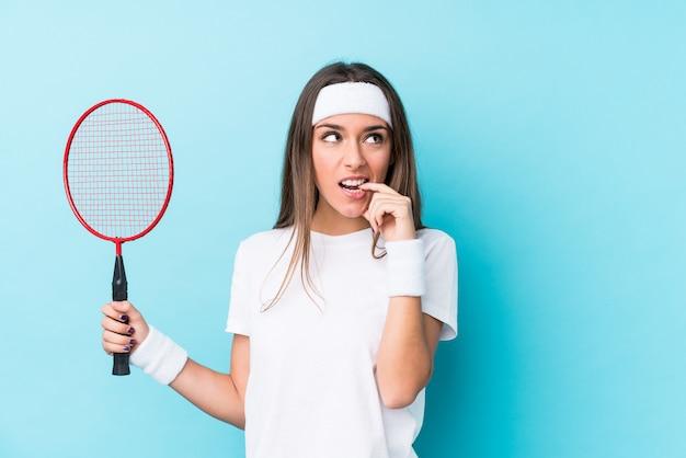 Młoda caucasian kobieta bawić się badminton odizolowywał zrelaksowanego główkowanie o coś patrzeje odbitkową przestrzeń.