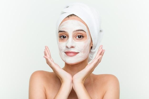 Młoda caucasian kobieta cieszy się offacial maskowego traktowanie