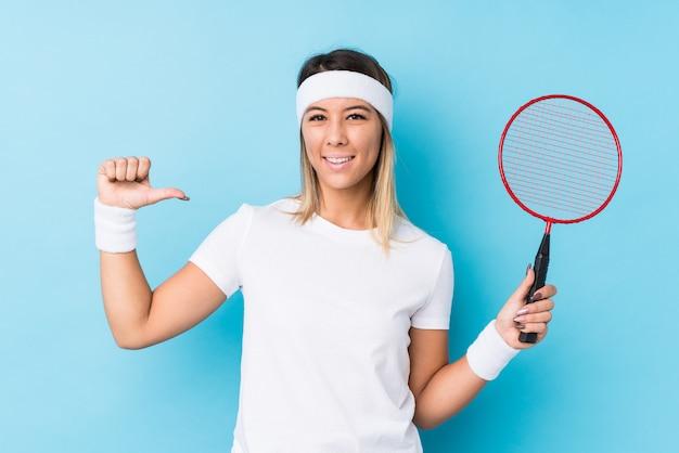 Młoda caucasian kobieta grająca w badmintona na białym tle czuje się dumna i pewna siebie, przykład do naśladowania.
