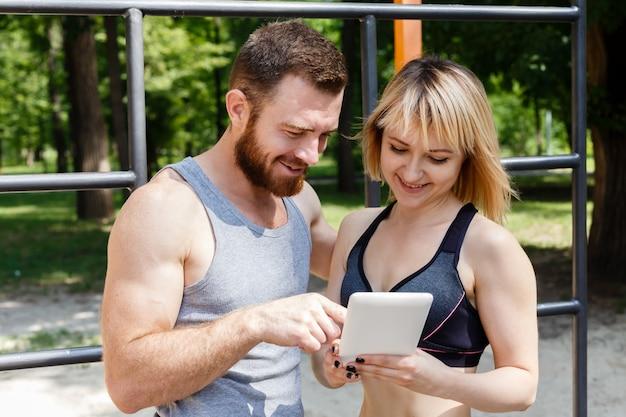 Młoda caucasian kobieta i brodaty mężczyzna przegląda internet na pastylka pececie podczas gdy robić sprawności fizycznych ćwiczeniom w parku.