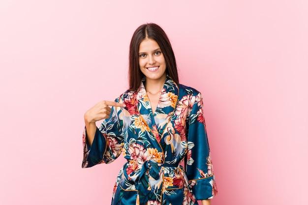 Młoda caucasian kobieta jest ubranym kimonową piżamy osobę wskazuje ręcznie do koszulowej kopii przestrzeni, dumny i ufny