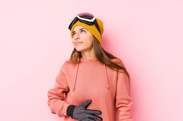 Młoda caucasian kobieta jest ubranym narciarskich ubrania odizolowywających dotyka brzuszek, uśmiecha się delikatnie, je i satysfakci pojęcie.
