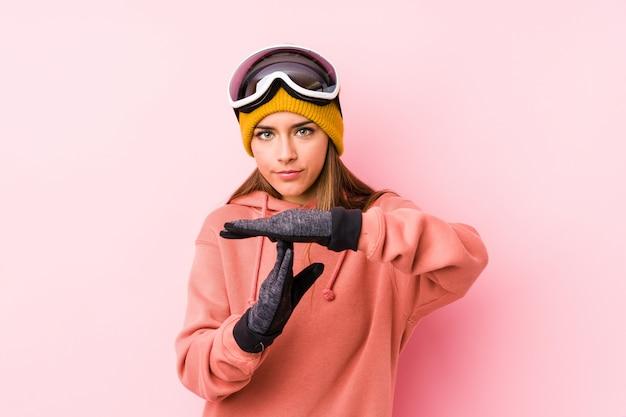 Młoda caucasian kobieta jest ubranym narciarskiego odziewa pokazywać timeout gest.