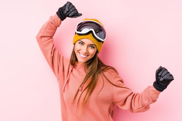 Młoda caucasian kobieta jest ubranym narciarskiego ubrania odizolowywającego świętujący specjalnego dzień, skacze i podnosi ręki z energią.