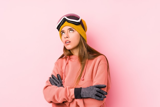 Młoda caucasian kobieta jest ubranym narciarskiego ubrania odizolowywającego zmęczonego powtarzalny zadanie.