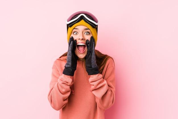 Młoda caucasian kobieta jest ubranym narciarskiego ubrania odizolowywał krzyczeć excited przód.