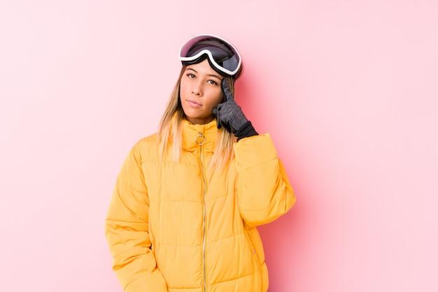 Młoda caucasian kobieta jest ubranym narciarskiego ubrania w różowej ściany wskazuje świątyni z palcem, myśleć, skupiający się na zadaniu.