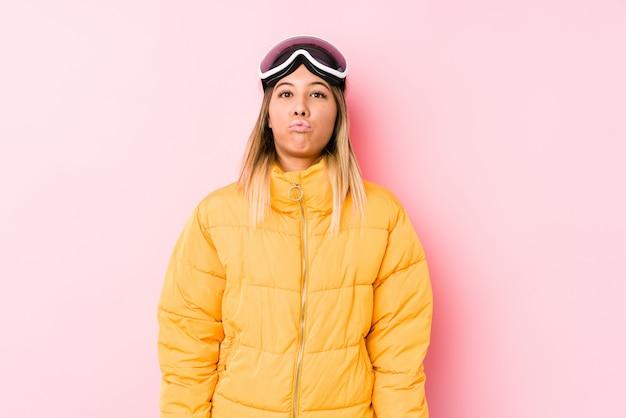 Młoda caucasian kobieta jest ubranym narciarskiego ubrania w różowym tle dmucha policzki, ma zmęczonego wyrażenie. koncepcja wyrazu twarzy.