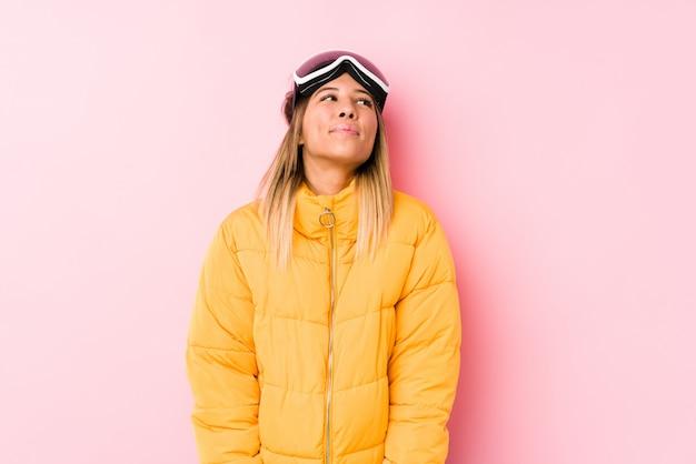 Młoda caucasian kobieta jest ubranym narciarskiego ubrania w różowym tle marzy o osiąganiu celów i celów