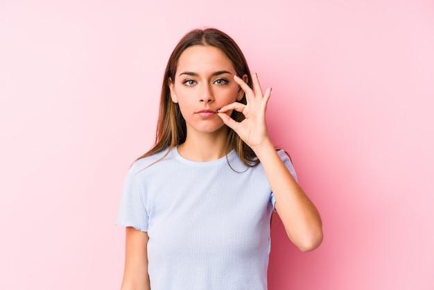 Młoda caucasian kobieta jest ubranym narta odziewa z palcami na wargach utrzymuje sekret.