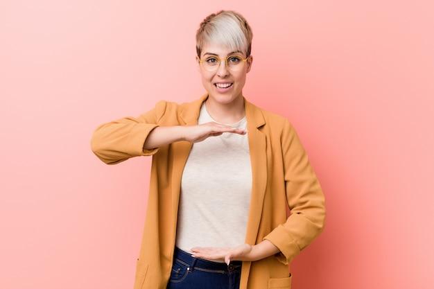 Młoda caucasian kobieta jest ubranym przypadkowego biznesu odzieżowego mienie coś z oba rękami, prezentacja produktu.