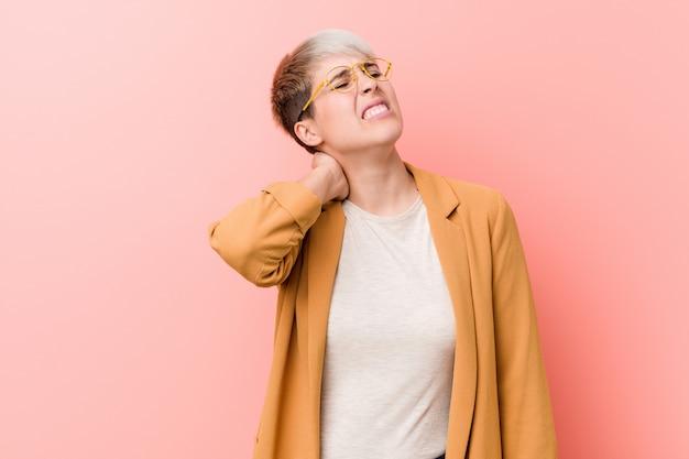 Młoda caucasian kobieta jest ubranym przypadkowego biznesu ubrania cierpi ból szyi z powodu siedzącego trybu życia.