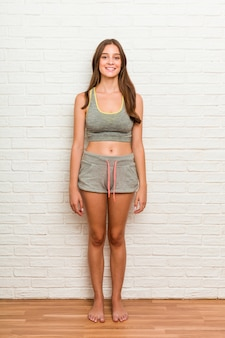 Młoda caucasian kobieta jest ubranym sport odziewa przeciwbrickswall