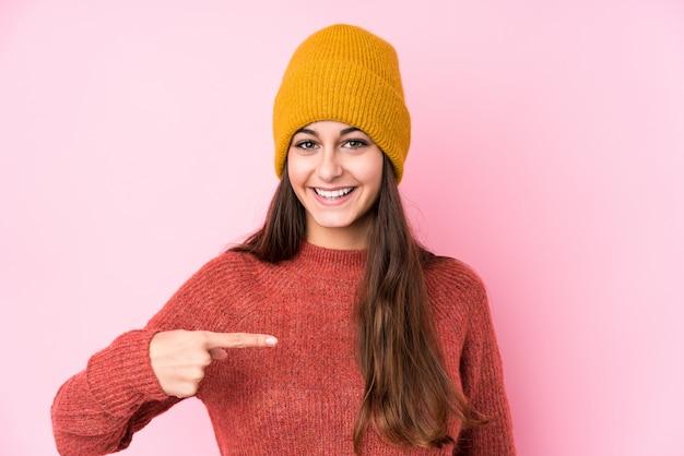 Młoda caucasian kobieta jest ubranym wełnianej nakrętki osoby wskazuje ręcznie do koszula kopii przestrzeni, dumny i ufny