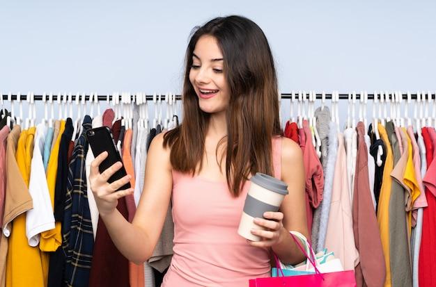 Młoda caucasian kobieta kupuje niektóre odziewa w sklepie trzyma kawę zabrać i wiszącą ozdobę