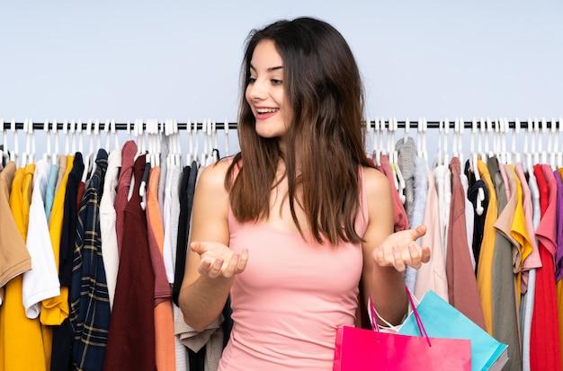 Młoda caucasian kobieta kupuje niektóre odziewa w sklepie z niespodzianka wyrazem twarzy