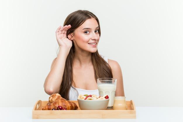 Młoda caucasian kobieta ma śniadanie próbuje słuchać plotki.