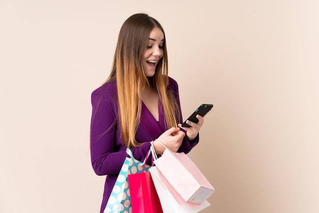 Młoda caucasian kobieta na beżowej ścianie trzyma torba na zakupy i pisze wiadomości z jej telefonem komórkowym przyjaciel